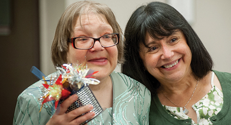 Woman with developmental disability holds a handmade centerpiece and smiles with a member of her staff.