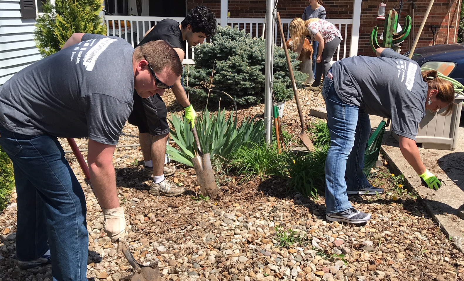 Volunteers in matching shirts use shovels and hand tools to clean up mulch and landscaping at a group home.