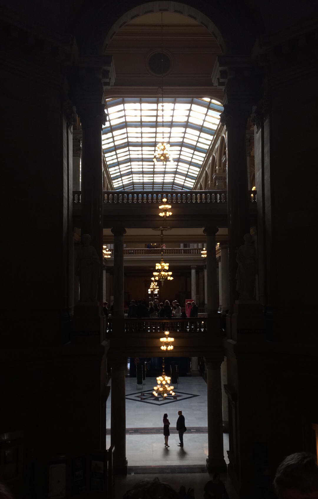 A man and woman are silhouetted at the bottom of the grand staircase at the Indiana State House.