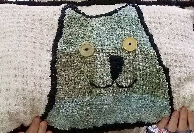 A handmade white pillow sporting a green cat head with tan button eyes.