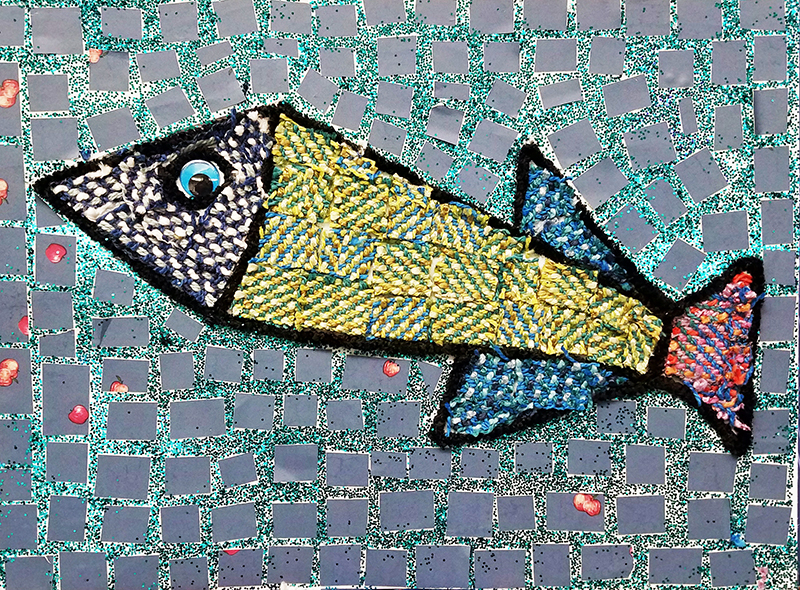 A mixed-media mosaic fish in yellow, blue, white and red.