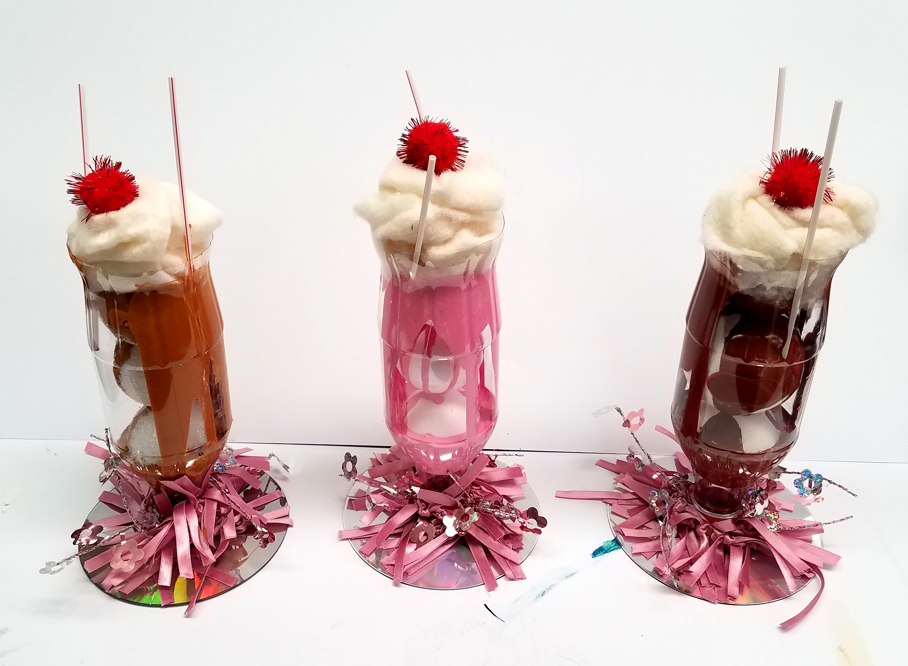 Three-dimensional art pieces made to look like ice cream sundaes, but created from non-edible materials like strips of paper and foam.