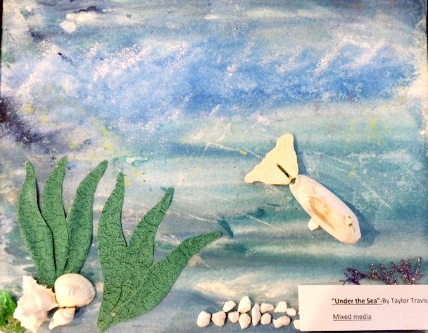 Mixed-media artwork depicting a blue underwater scene with a white and yellow fish and white rocks and seashells.