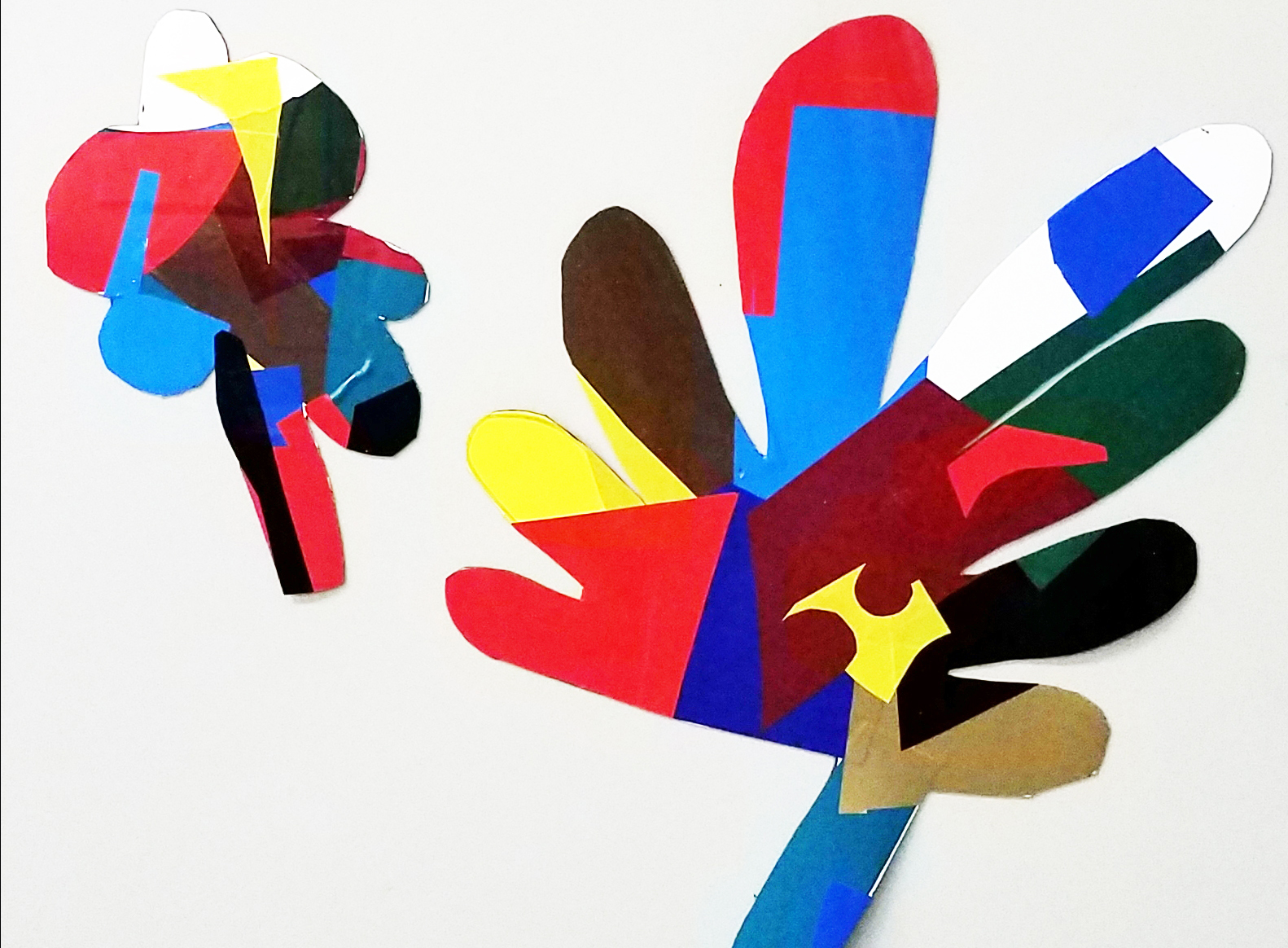 Artwork in the shape of two colorful leaves in blue, red, brown, yellow, white and green.