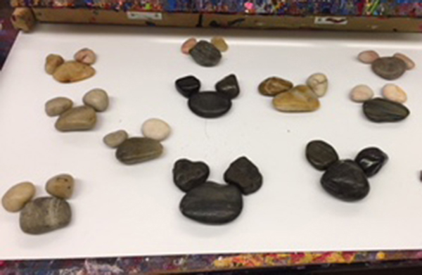 Eleven different rock formations shaped like Mickey Mouse heads and placed spread out on a table.