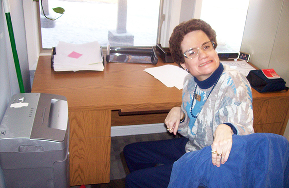 A woman with developmental disabilities sitting in a coat-draped chair takes a break from the paperwork on the desk to look around and smile at the camera.