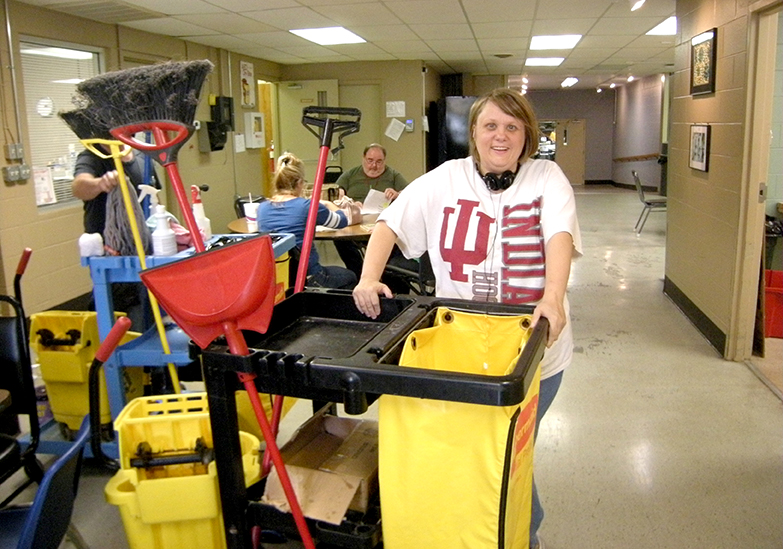 A smiling young woman with developmental disabilities wearing an Indiana University shirt stands behind her janitorial cart packed with brooms, a yellow bag and a yellow mop bucket.