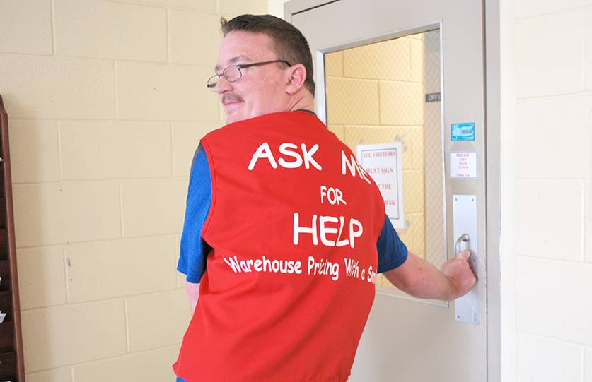 A young man with developmental disabilities shows off the back of his vest that reads