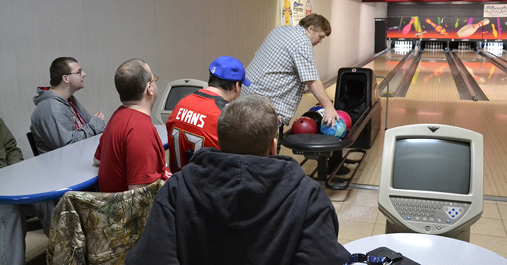A group of friends in a bowling alley sit and watch as a man picks up his bowling ball to roll a shot.