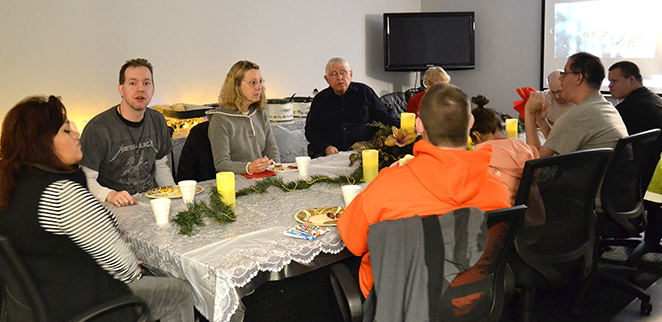 Men and women sit around a table and eat a holiday breakfast at a day program facility.