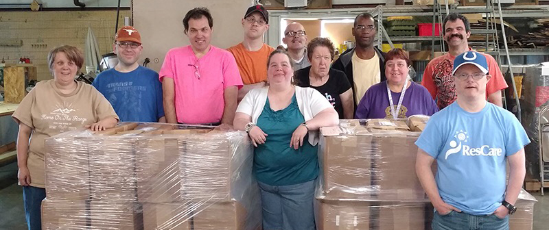 A group of men and women with developmental disabilities pose in front of plastic-wrapped boxes of product they have manufactured and prepared for shipment.