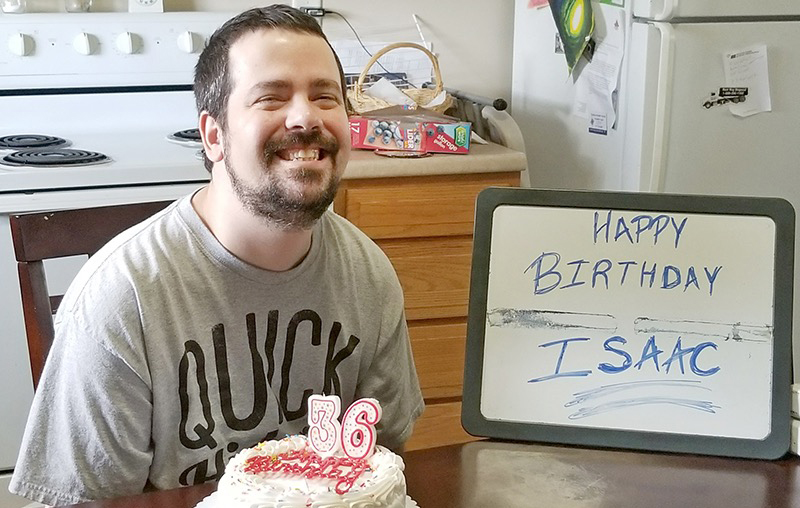 A young man smiles broadly behind a white cake with candles and a sign wishing him happy birthday.