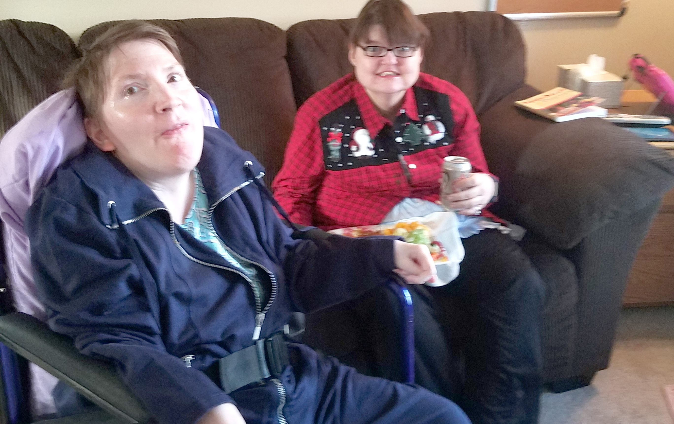 A woman in a wheelchair and her friend, sitting on a couch with a plate of food and a drink, smile at the camera.