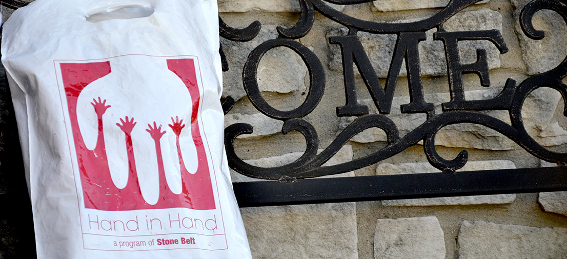A white bag with a red logo depicting outstretched hands rests on a black wrought-iron bench outside a stone-sided house.