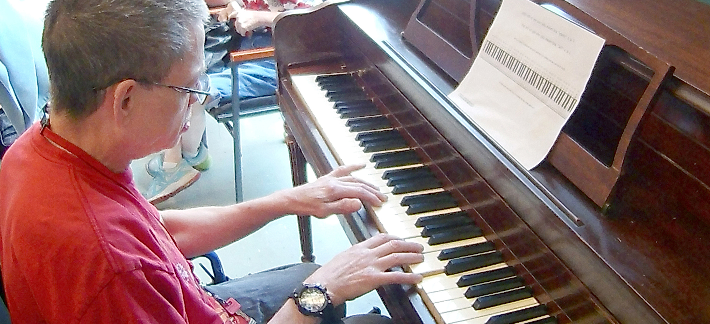 A man with a developmental disability plays the piano at day program.