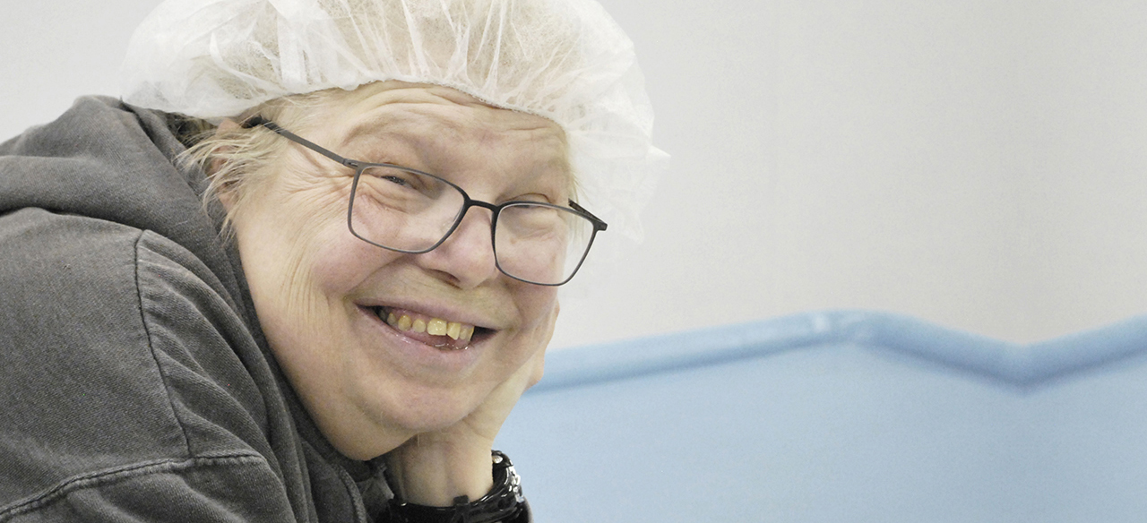 A woman with developmental disability wears glasses and a hairnet and smiles into the camera.