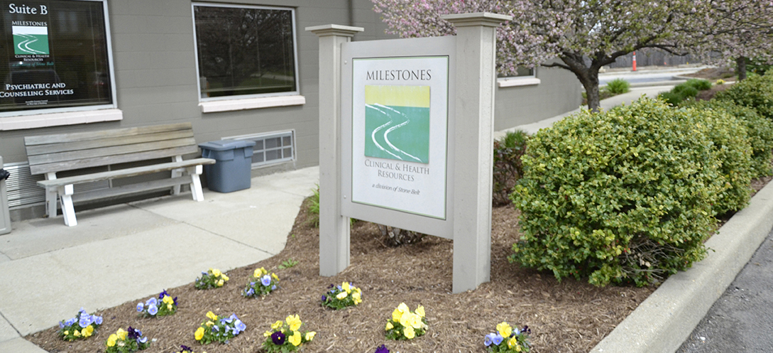 A large yard sign surrounded by yellow flowers and trimmed bushes marks the location of Milestones clinic in Bloomington, Indiana.