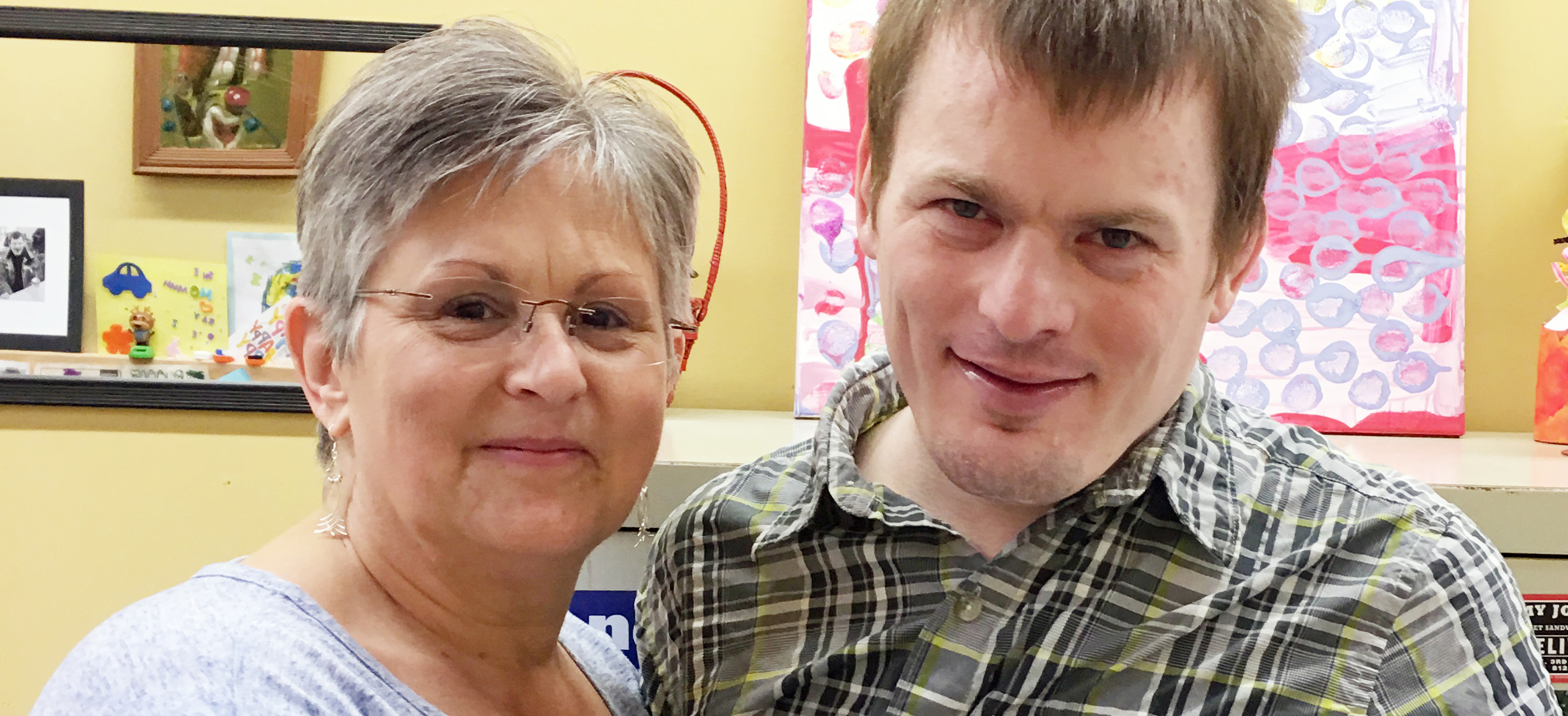 A mother and her son with developmental disabilities stand together and smile.