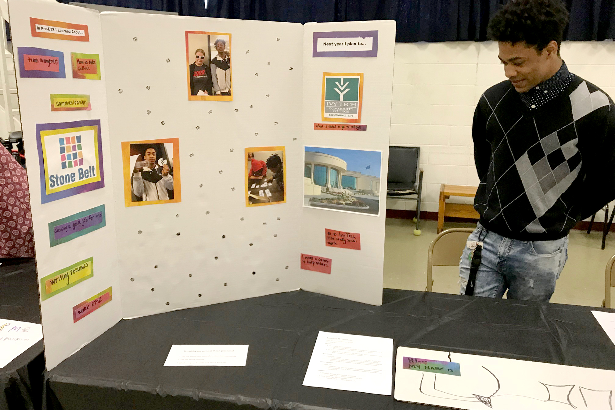 A young man stands behind a table and next to his poster, waiting for visitors to his Pre-ETS booth.