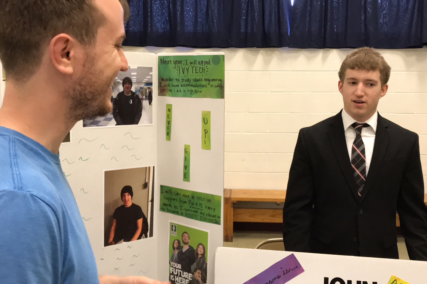 A young man in a suit behind a table talks with a smiling man in a blue shirt about his experience with the Pre-Employment Transition Services program.