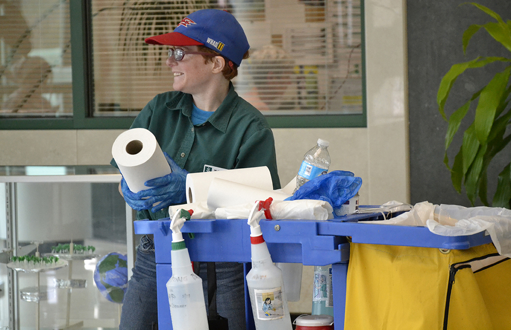 A young woman with red hair, a baseball cap and a green shirt, holding a role of paper towels behind her janitorial cart, smiles and looks left at the distance.